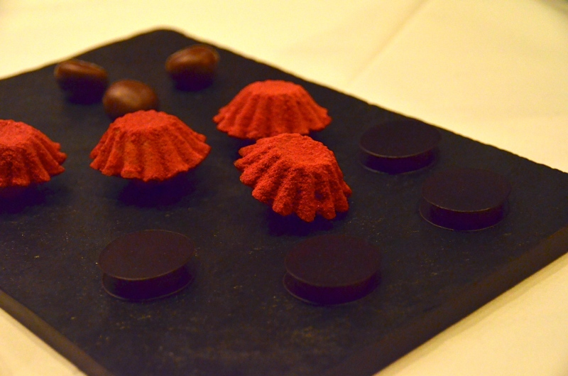 Mignardises: Nocino-filled chocolate, raspberry powder-dusted financiers and chocolate paper with caramel.